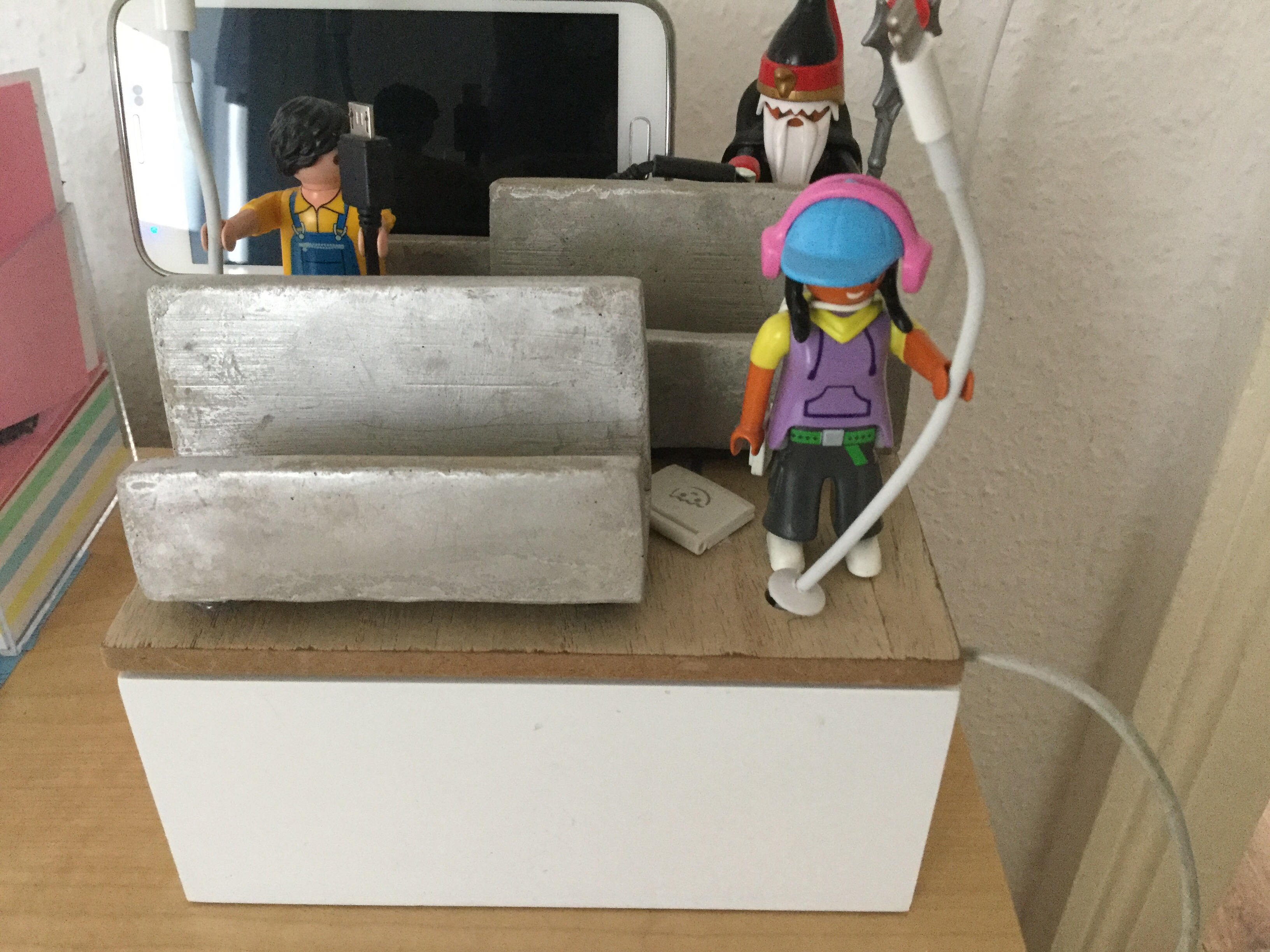 Ladestation, weißes Kästchen mit drei Handy-Ruhebänken und Playmobil-Figuren, die die Ladekabel halten
